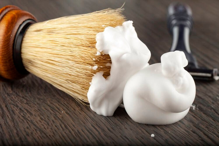 a close-up on a shaving cream and a brush