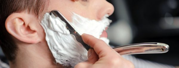 Skillful barber. Young man getting an old-fashioned shave with straight razor
