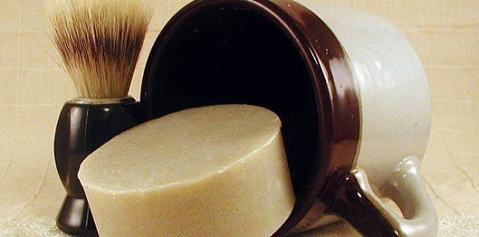 a round shaving soap and a shaving brush