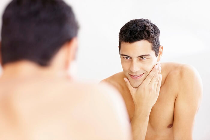 naked man looking at himself in the mirror with satisfaction after shaving