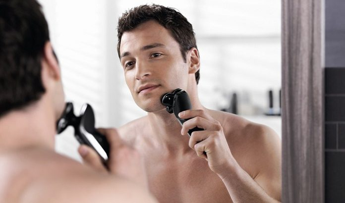 man using electric shaver