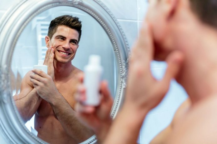 man applying aftershave to his face
