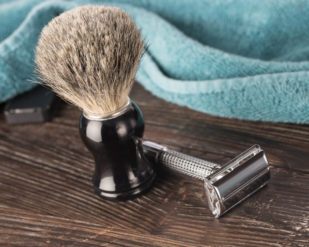Double edged razor in bathroom setting prepared for a wet shave with a badger hair shaving brush and towel
