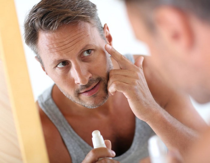 men in the bathroom mirror, applying a pre shave oil