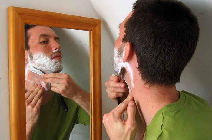 a man shaving in the mirror