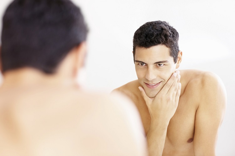 a young shaved man looking in the mirror