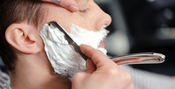 a barber shaving a man with a straight razor
