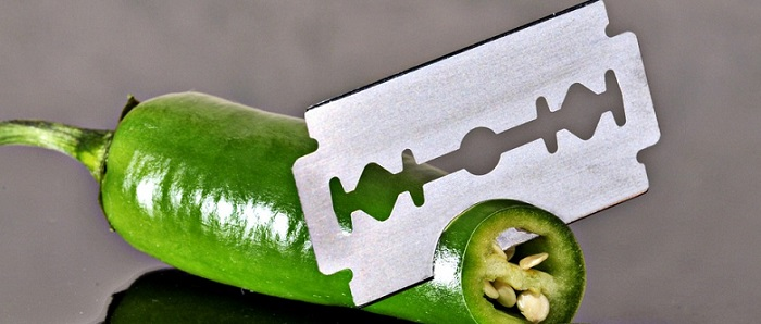 a sharp razor blade cutting a green hot pepper