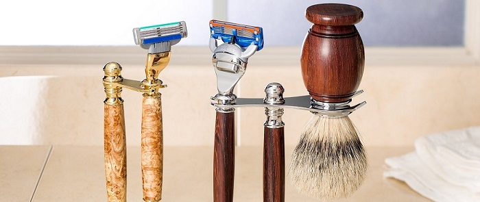 a vintage-looking shaving kit with a shaving brush and two razors on a standing support