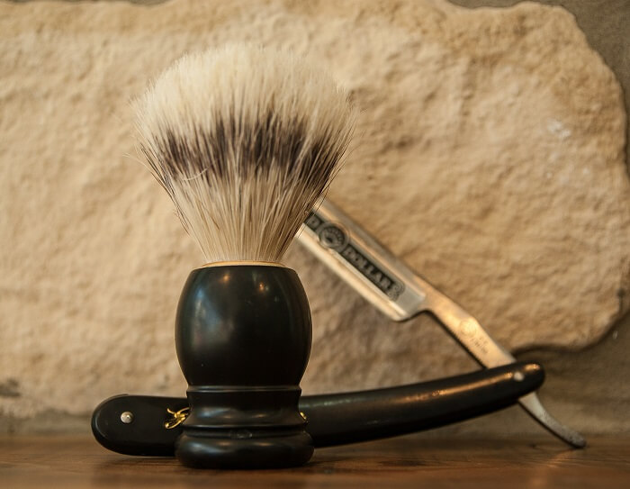 traditional straight razor with its case and a shaving brush