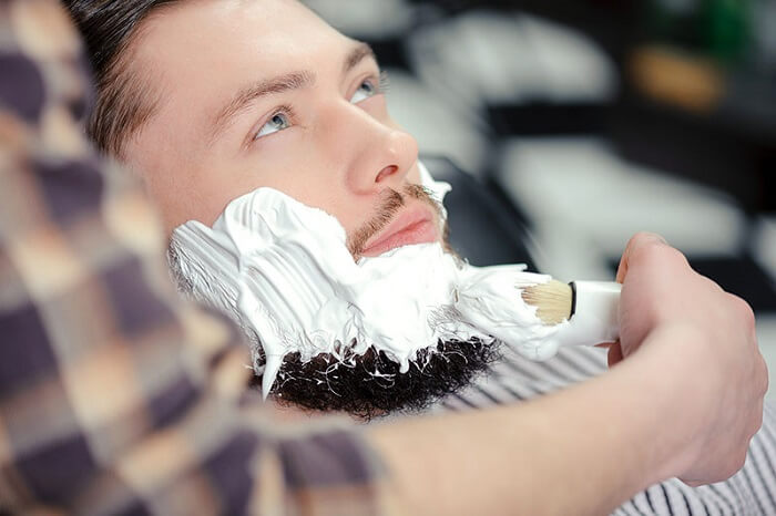 barber applies shaving cream on client with thick beard