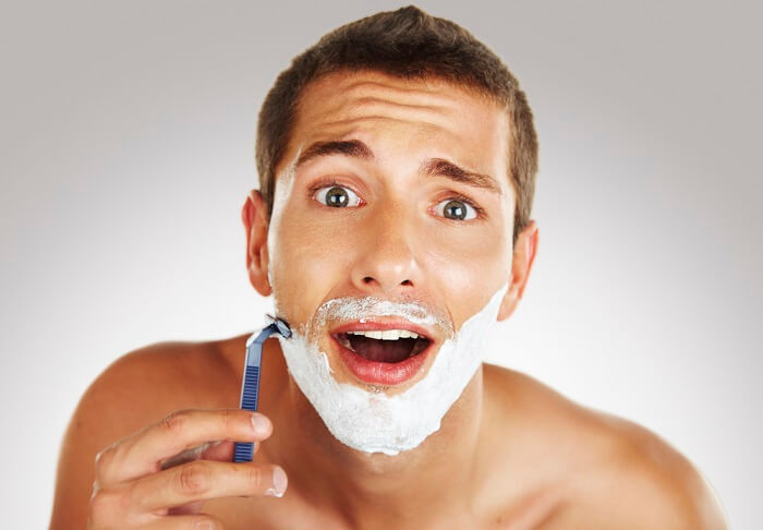 man shaving with gel and razor in front of mirror