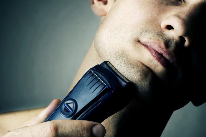 male model shaving chin with electric razor