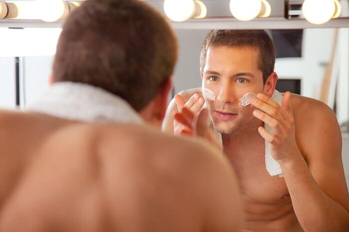 naked male model in bathroom applies face moisturizer while looking in the mirror