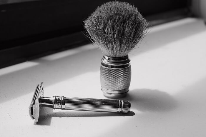 shaving brush and shaving razor on white surface