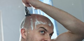 man shaving head with razor