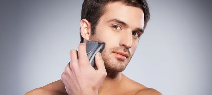 man shaving his face with an electric shaver