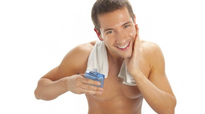 Young man applying after shave