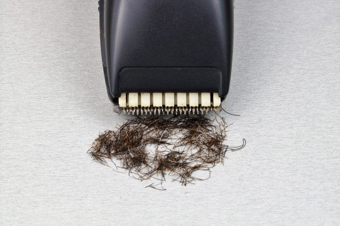 Black razor near a pile of hair