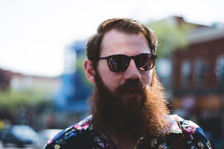 man wearing sunglasses with patchy beard