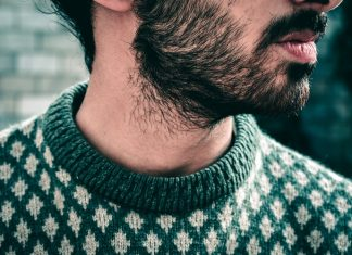 man wearing green sweater with patchy beard